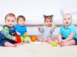 Four babies sitting in the carpet with their toys